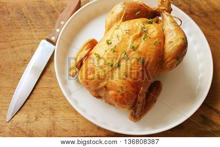 Roasted whole  chicken on wooden background .