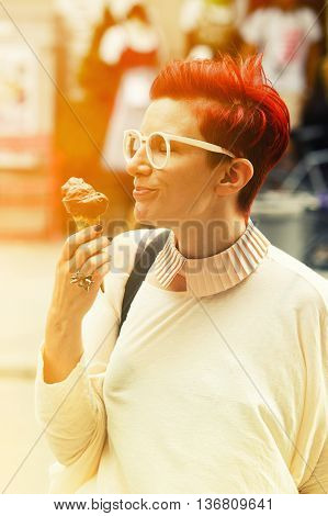 red-haried woman standing in the streets and eating chocolate icecream