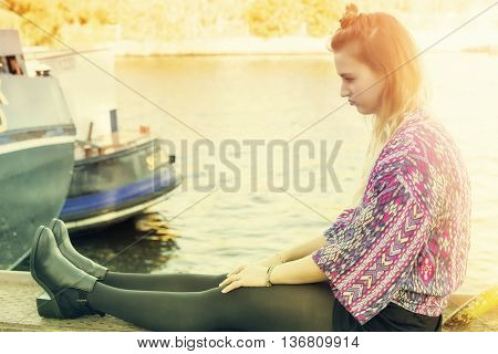 young woman sitting by the water and pouting
