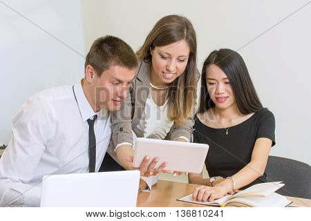 Multicultural team looking at a tablet at the office