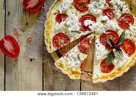 The Classic Quiche Lorraine Pie With Soft Feta Cheese And Tomatoes In A Baking Dish On A Wooden Back