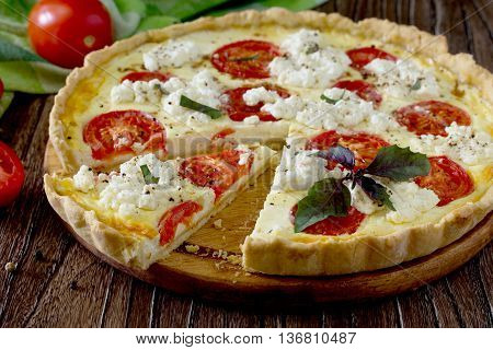 The Classic Quiche Lorraine Pie With Soft Feta Cheese, Basil And Tomatoes In A Baking Dish On A Wood