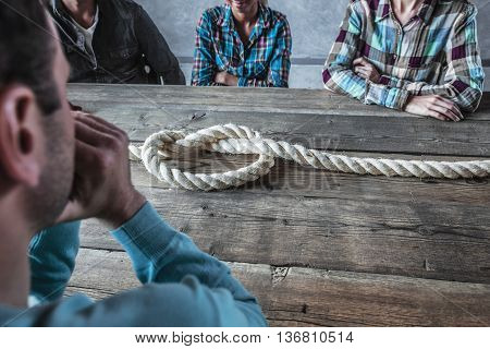 People sitting around the table with rope node on it business problem concept