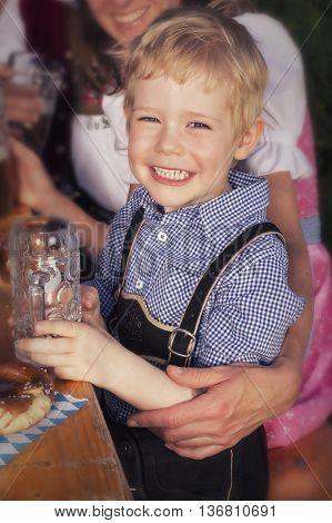 young blond bavarian boy at Oktoberfest smiling at camera