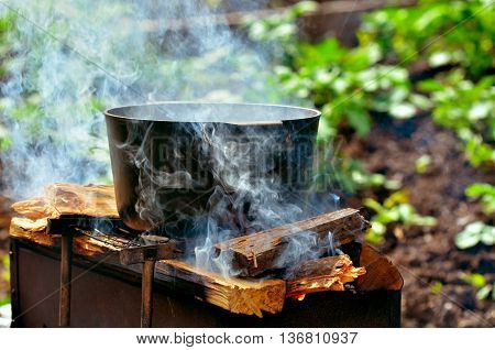 Preparing food on campfire.Outdoor summer. Fish soup cooking in a pot on a fire.