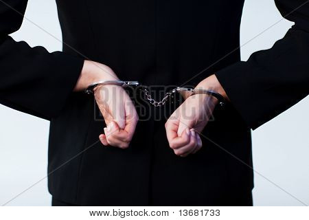 Business person handcuffed behind back