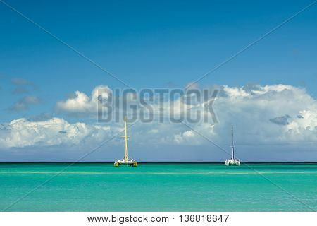 Catamarans moored in front of a tropical beach