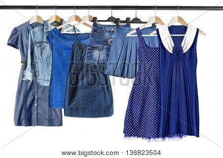 Group of blue clothes on clothes racks isolated over white