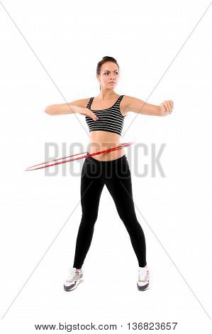 Slim young woman dressed in black and white stipped top and black leggins training with red hula hoop smiling isolated on white background
