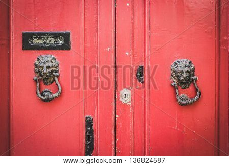 Old Red Wooden Doors with a Pair of Lion Head Metal Knockers in Mdina Malta