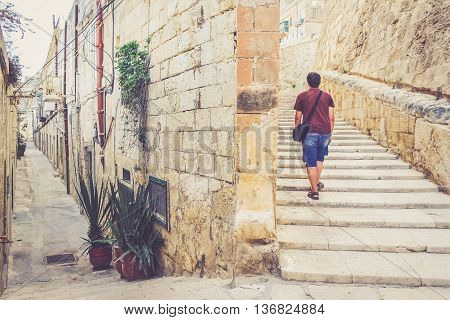 Stairs on the street of la Valletta Malta. Man has chosen the way going up the stairs. Moving up to Success concept