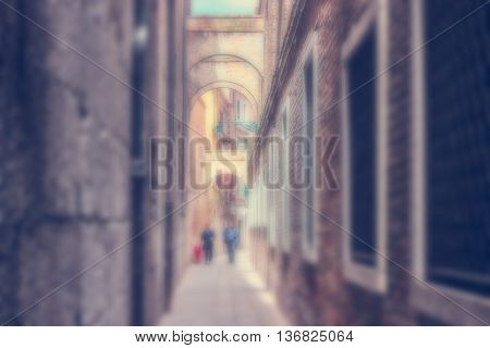Defocused Background with two Men walking down the Ancient narrow Street of Venice Italy