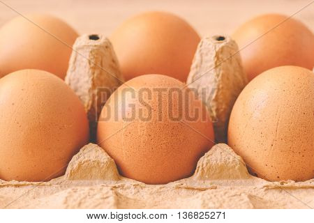 Six chicken eggs in cardboard box retro toned selective focus