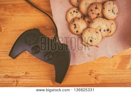 Gamepad and homemade chocolate chip cookies on rustic wooden table top view concept of childhood memories and nostalgia.