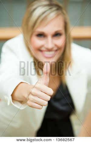 Businesswoman smiling with her thumbs up in an office