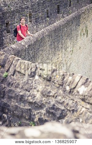 Tourist man is standing on the medieval fortress wall in Luxembourg's Grund Valley