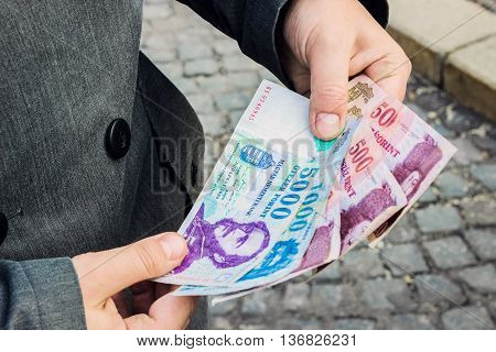 Close up with man standing on the cobblestone street and holding money banknotes of Hungarian Forint currency in his hands