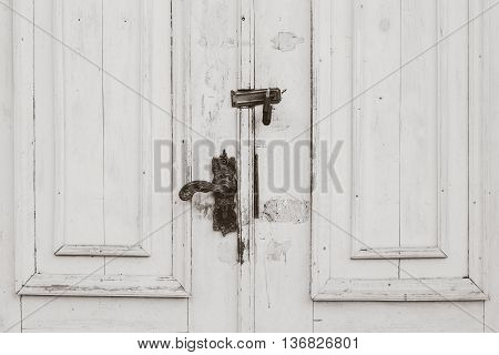 Old distressed white doors close up with black metal handle and lock