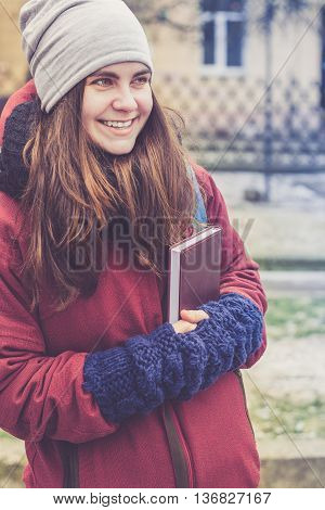 Beautiful hipster girl with long brown hair holding book in her hands in winter clothes outdoor (wearing grey hat red jacket black knitted scarf and blue mittens)