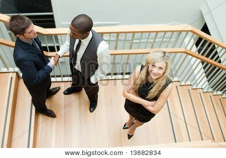 High view of two businessmen shaking hands and a businesswoman with folded arms smiling at the camera