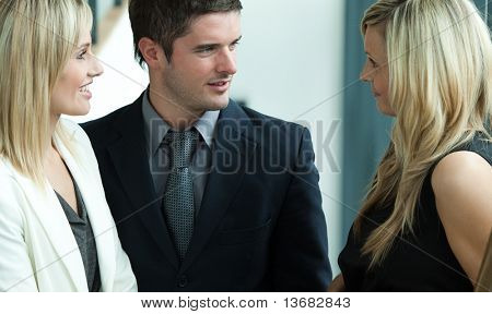 Handsome businessman speaking with two blonde businessswomen