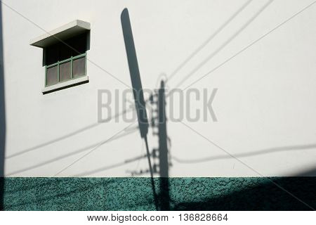 shadows of Lamp post and a window on a white background with green