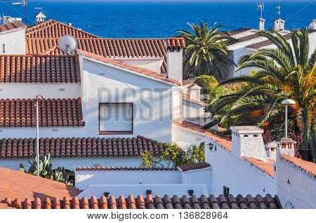 Housetops from terracotta tiles palm trees blue sea. Travel destination. Costa Dorada Spain. Horizontal.