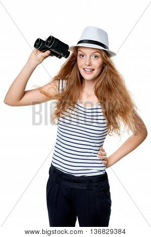 Young beautiful teen female in striped tee and white straw fedora hat holding binoculars and looking at camera smiling happy, over white background