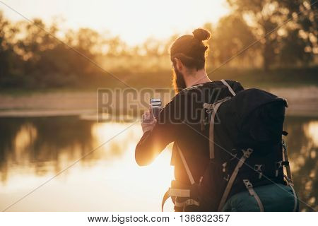 Backpacker photographing a lake landscape with his smartphone