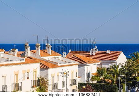 Small mediterranean snug resort town on Costa Dorada Spain. Chalets beside the sea. Summer vacations concept. Horizontal.