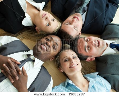 Closse-up of Business people lying in a circle on the floor of the office