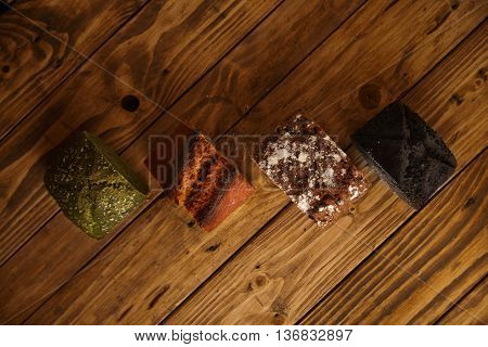 Pieces of different professional baked breads presented on wooden table as samples for sale: pistachio, dry tomato, lavender and coal. Top view