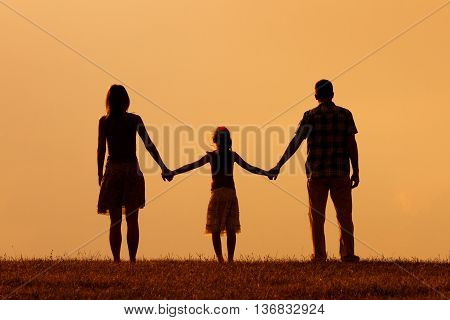 Parents enjoy watching sunset with their daughter.