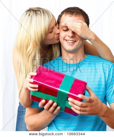 Young woman giving a present to her husband surprising him