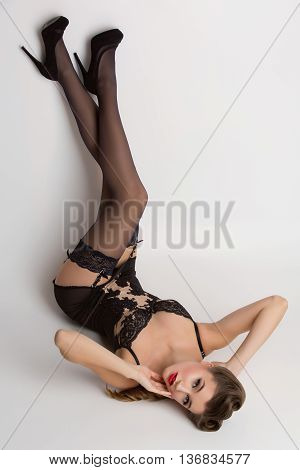 Beautiful retro pinup girl with red lips in black lace lingerie. Studio shot. Copy space.