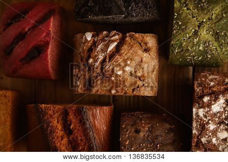Many mixed alternative baked breads presented as samples for sale on rustic wooden table in professional bakery: pistachio, beetroot, tomatoes, lavender, sea salt, coal, sweet potato Close up