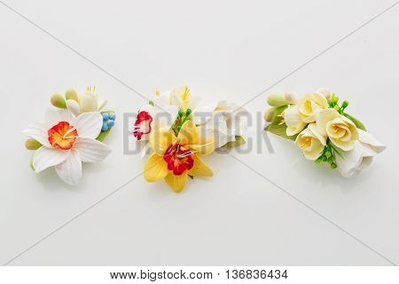 Beautiful handmade art clay spring flower bouquets. Bridal accessory. Boutonniere. Over white background.