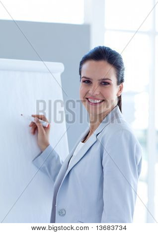 Smiling businesswoman writing in a whiteboard in office