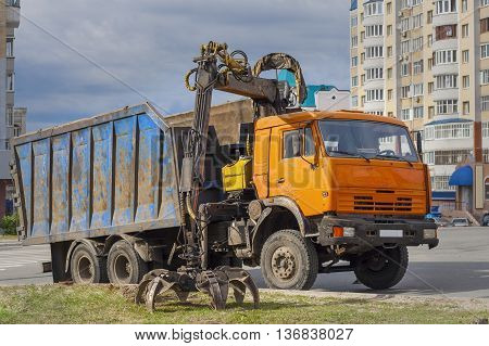 Old truck for transportation and loading of scrap in the city moved the tongs to grip scrap iron.