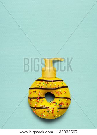 Creative still life of a tasty sweet yellow donut with a cosmetic pump dispenser on blue background.
