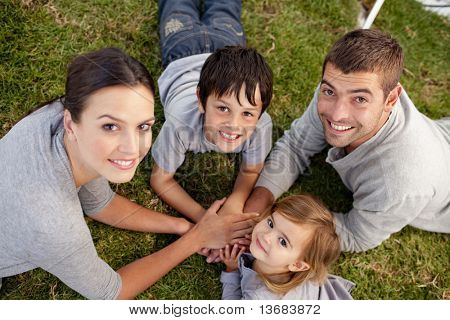 Happy parents and kid lying on garden