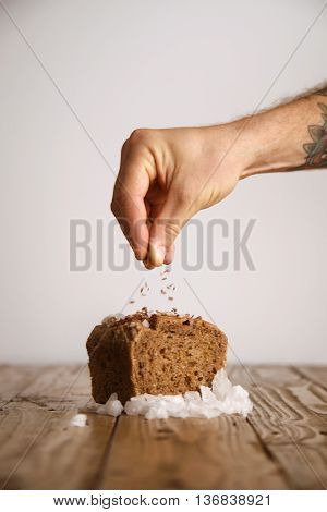 Hand pours lavender seeds on rye bread with sea salt organically baked in artisan bakery, presented on wooden rustic table and white background