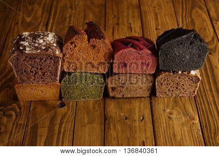 Many mixed alternative baked breads presented as samples for sale on rustic wooden table in professional bakery All tasty, healthy and organic