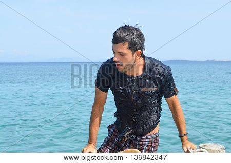 Wet Man Climbing The Dock At The Seaside
