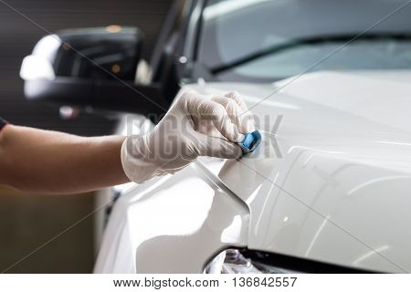 Car detailing series : Closeup of hand coating white car bonnet