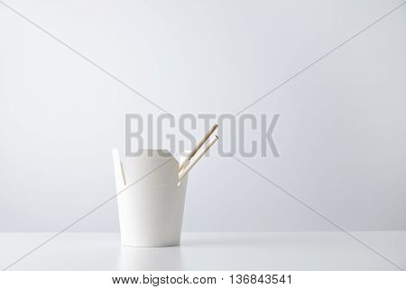 Blank takeaway noodle box with chopsticks inside presented on side and isolated on white mockup