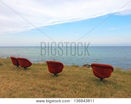 Four red retro armchairs by the sea