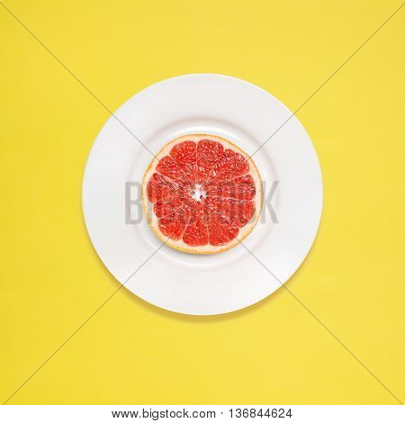 Red grapefruit slice on white plate on yellow background.
