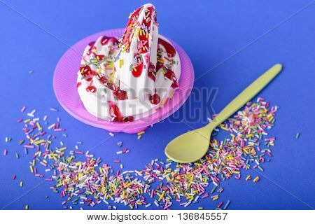 frozen yogurt with black cherry topping and rainbow sprinkles on blue background with yellow spoon and rainbow sprinkles