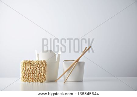 Opened and closed takeaway boxes, brick of fast food noodles presented with chopsticks, isolated on white Retail set